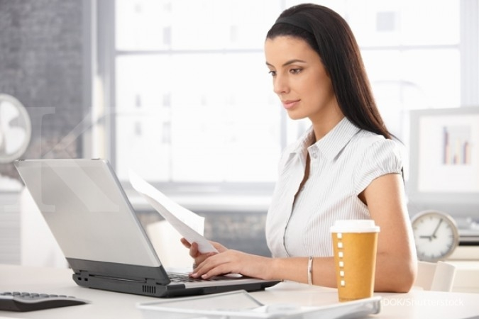 Attractive woman sitting at desk in office, working with laptop computer, holding document, having takeaway coffee. Foto: DOK Shutterstock