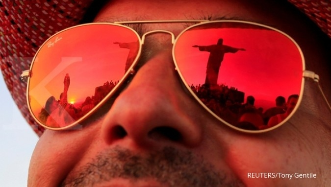 FILE PHOTO: The statue of Christ the Redeemer is reflected in the Luxottica owned Ray Ban sunglasses, of a tourist in Rio de Janeiro, Brazil, June 8, 2014. REUTERS/Tony Gentile/File Photo