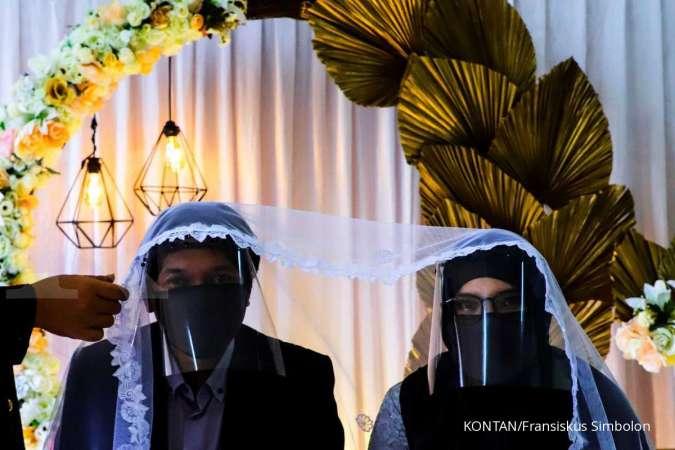 JAKARTA,06/06-AKAD NIKAH DI PSBB TRANSISI. Pasangan pengantin Thomas Rudyanto (kiri) bersama Dian Larasati (kanan) menggunakan sarung tangan, masker, dan pelindung wajah saat melaksanakan prosesi akad nikah di Kantor Urusan Agama (KUA) Ciracas, Jakarta, S