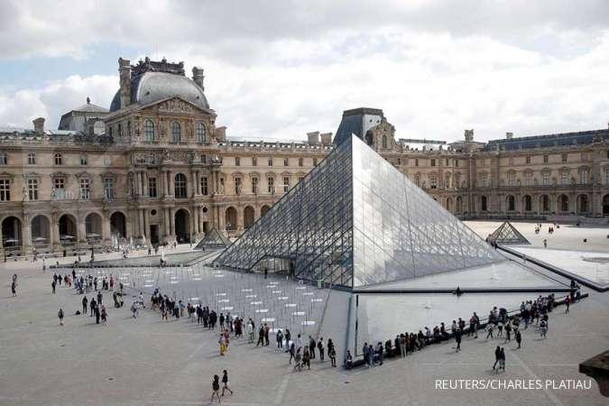 ILUSTRASI. Pengunjung mengantre untuk memasuki Piramida Louvre di Paris, ketika museum ini membuka kembali pintunya untuk umum setelah hampir 4 bulan tutup karena wabah penyakit virus corona (COVID-19) di Prancis, 6 Juli , 2020.