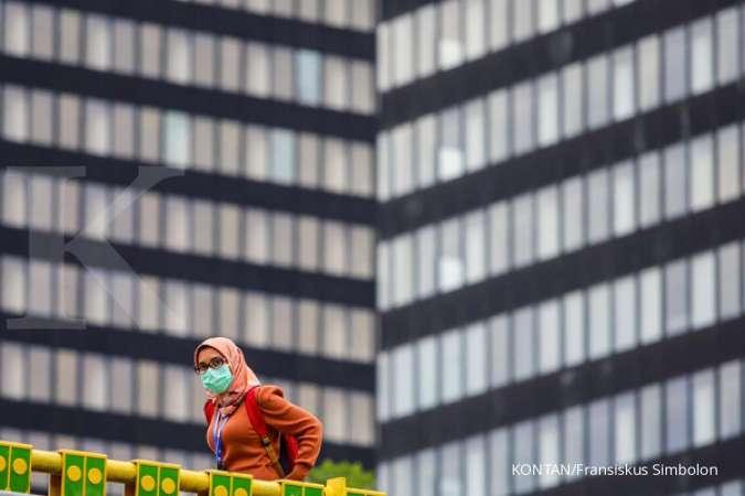 Pekerja dengan menggunakan masker melintas di kawasan Stasiun Sudirman, Jakarta, Jumat (8/1/2021).