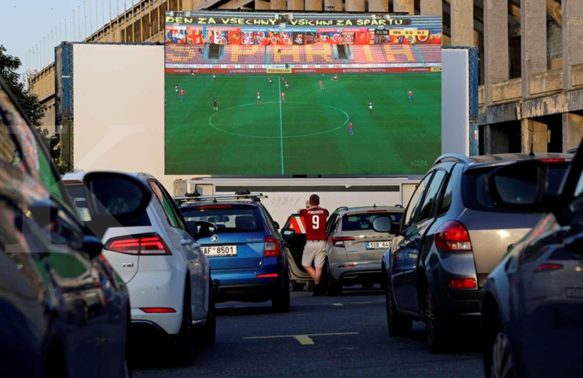 Menonton pertandingan sepak bola melalui bioskop drive-in