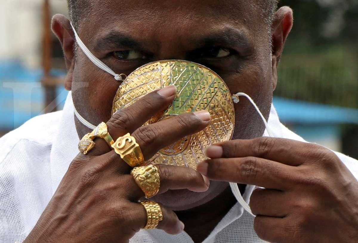 Pria ini mengenakan masker emas untuk tangkal corona